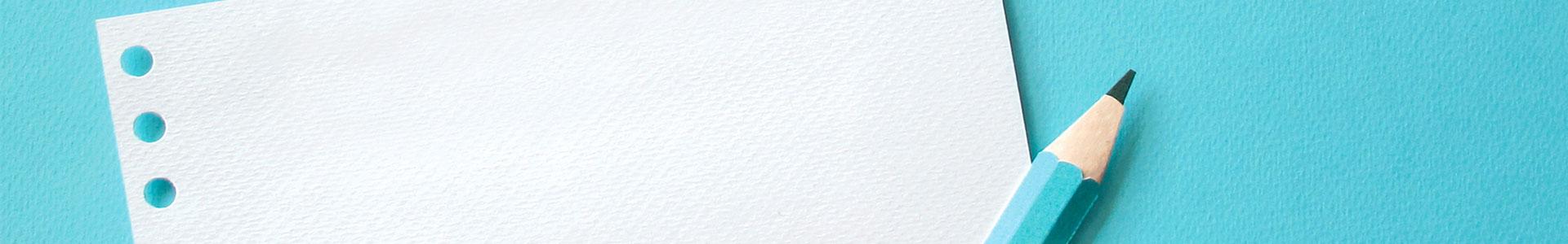 Bleistift und Papier auf türkisem Hintergrund